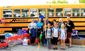 Group photo of donated school items on Fill Up the Bus day