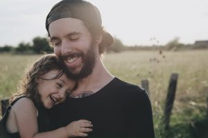 Young man and his daughter smiling