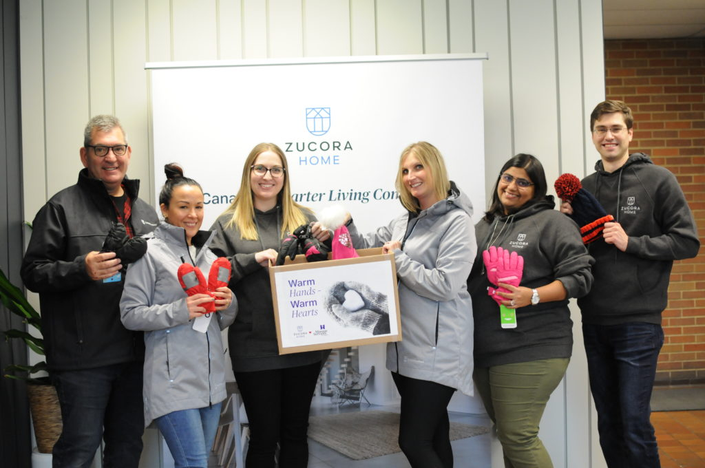 Zucora Home staff filling up a box of warm winter wear to donate to children in need