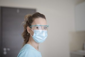 Woman wearing surgical face mask and clear plastic face shield