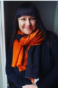 Jennifer Vale smiling by window wearing bright orange scarf